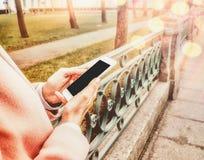 Fermez du téléphone de cellules de participation de mains du ` s de femmes avec l'éboulis vide de l'espace de copie votre message Photographie stock