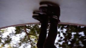 Fermez la longueur d'un homme dans des vêtements sport monte des patins de rouleau en parc de patin sur la rampe Patins de roulea banque de vidéos