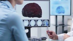 Fermez la longueur des mains de docteur montrant à une simulation du cerveau 3D clips vidéos