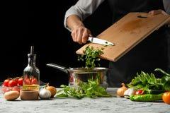 Fermez le chef& x27 ; mains de s, préparant une sauce tomate italienne pour le mA photo stock