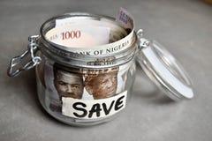 Fermez vers le haut du Nigerian mille notes de naira dans le pot de l'épargne Photo stock