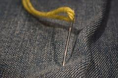 Fermez-vous, aiguille et fil jaunes sur le tissu de jeans Photographie stock