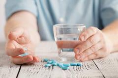 Fermez-vous avec la pilule et le verre de l'eau en main, concept de médecine, foyer sélectif photos stock