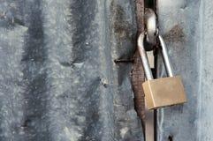 Fermez-vous, cadenas avec la vieille barrière de fer ondulé photos stock