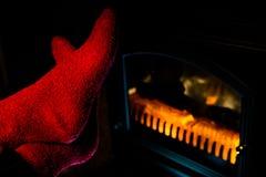 Fermez-vous d'étirer des pieds dans les chaussettes rouges par la cheminée Photos stock