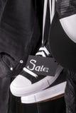 Fermez-vous d'accrocher les espadrilles noires et blanches avec la vente de signe près du chapeau de jeans sur le fond Vendredi Images stock