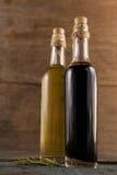 Fermez-vous d'huile d'olive dans des bouteilles avec l'herbe Photos libres de droits