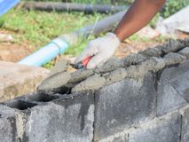 Fermez-vous d'installer des briques dans le chantier de construction par le maçon industriel images stock