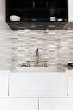 Fermez-vous d'un évier de cuisine blanc profond et d'un revêtement carrelé images stock