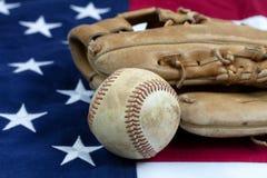 Fermez-vous d'un base-ball et d'un gant utilisés sur le drapeau des Etats-Unis Photo stock