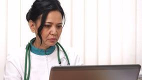 Fermez-vous d'un beau docteur mûr féminin asiatique travaillant sur son ordinateur portable photo libre de droits