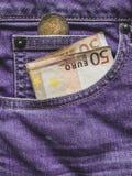 Fermez-vous d'un billet de banque de l'euro 50 dans une poche photos stock