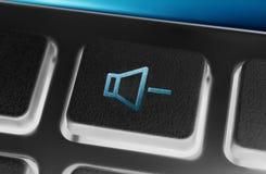 Fermez-vous d'un bouton noir de volume vers le bas d'un noir à télécommande avec le contre-jour image stock