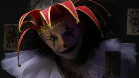 Fermez-vous d'un clown rampant avec le maquillage et le vieux chapeau avec des cloches, cartes flottent dans le ciel banque de vidéos