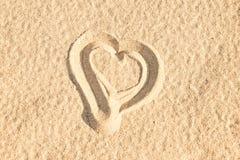 Fermez-vous d'un coeur dans le sable d'une plage Photographie stock libre de droits