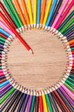 Fermez-vous d'un crayon rouge se tenant d'un cercle de beaucoup de crayons colorés Images stock