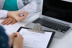 Fermez-vous d'un docteur et d'un patient s'asseyant au bureau tandis que médecin se dirigeant dans l'ordinateur portable La médec Photos stock