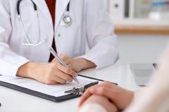Fermez-vous d'un docteur féminin remplissant vers le haut d'un formulaire de demande tout en consultant le patient Photos libres de droits