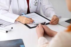Fermez-vous d'un docteur féminin remplissant vers le haut d'un formulaire de demande tout en consultant le patient image stock