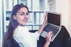 Fermez-vous d'un employé de bureau gai avec l'ordinateur portable image libre de droits