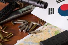 Fermez-vous d'un fusil de chasse et d'un revolver, ceinture de cartouche avec des balles avec le drapeau coréen du nord sur une c Image libre de droits