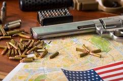 Fermez-vous d'un fusil de chasse et d'un revolver, ceinture de cartouche avec des balles avec un drapeau brouillé des Etats-Unis  Photographie stock libre de droits