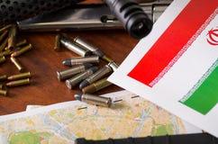 Fermez-vous d'un fusil de chasse et d'un revolver, ceinture de cartouche avec des balles avec un drapeau de l'Iran sur une carte, Photo libre de droits