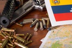 Fermez-vous d'un fusil de chasse et d'un revolver, ceinture de cartouche avec des balles avec un drapeau vénézuélien brouillé, su Photos libres de droits