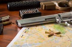 Fermez-vous d'un fusil de chasse et d'un revolver, ceinture de cartouche avec des balles sur une carte, sur la table en bois Photos libres de droits