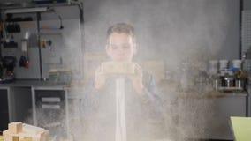 Fermez-vous d'un garçon en verres transparents soufflant loin la sciure dans le mouvement lent Enfants dans des professions adult banque de vidéos