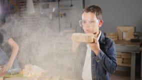 Fermez-vous d'un garçon en verres transparents soufflant loin la sciure dans le mouvement lent Enfants dans des professions adult clips vidéos