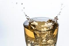 Fermez-vous d'un glaçon éclaboussant sur un verre de Ginger Ale photos stock