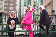 Fermez-vous d'un groupe heureux d'amis, attendant les différents costumes de transport en commun et de port, une femme Photo libre de droits