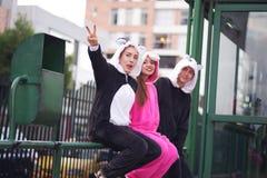 Fermez-vous d'un groupe heureux d'amis, attendant les différents costumes de transport en commun et de port, une femme Image libre de droits
