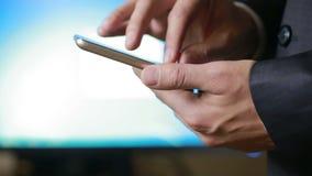 Fermez-vous d'un homme à l'aide du téléphone intelligent mobile le moniteur de fond banque de vidéos
