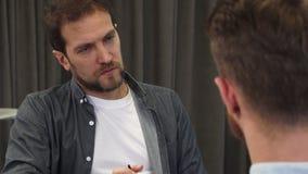 Fermez-vous d'un homme d'affaires mûr écoutant attentivement son collègue lors de la réunion banque de vidéos