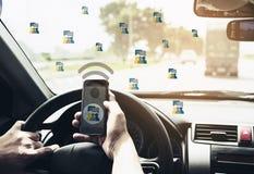 Fermez-vous d'un homme conduisant la voiture dangereusement tout en employant le pho mobile photographie stock libre de droits