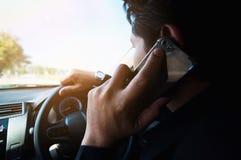 Fermez-vous d'un homme conduisant la voiture dangereusement utilisant le téléphone images libres de droits