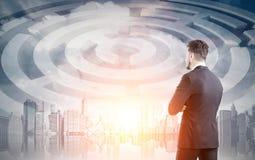 Fermez-vous d'un homme d'affaires dans une ville avec un labyrinthe Images stock