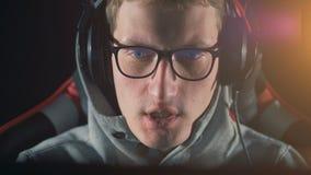 Fermez-vous d'un homme dans des écouteurs parlant le jeu de moment banque de vidéos