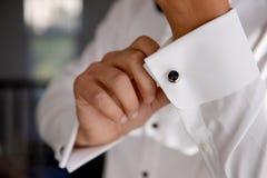 Fermez-vous d'un homme de main comment porte la chemise et le bouton de manchette blancs Photo stock
