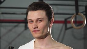 Fermez-vous d'un jeune athlète masculin souriant eau potable joyeux banque de vidéos