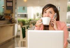 Fermez-vous d'un jeune beau coffe travaillant et potable de femme d'affaires tandis qu'elle utilise son téléphone portable pour f Photographie stock libre de droits