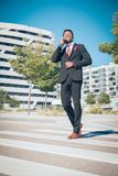 Fermez-vous d'un jeune et de l'homme d'affaires noir attirant passant par un passage pour piétons et parlant par téléphone devant photo stock