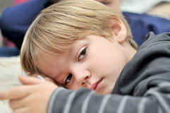 Fermez-vous d'un jeune garçon mignon se trouvant sur le lit Photo libre de droits