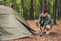 Fermez-vous d'un jeune touriste masculin blond installant une tente verte i Image stock