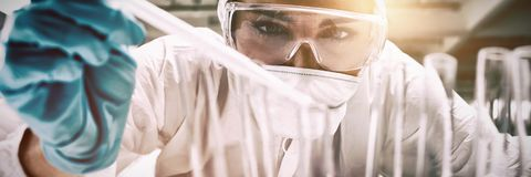 Fermez-vous d'un liquide de chute protégé d'étudiant de la science dans un tube à essai photos libres de droits