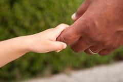 Fermez-vous d'un père et d'un fils tenant des mains Image stock