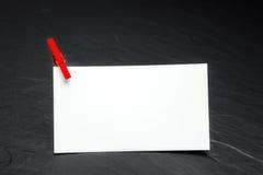Fermez-vous d'un papier de note et des pinces à linge Image stock