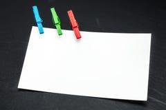 Fermez-vous d'un papier de note et des pinces à linge Photos libres de droits